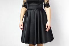 Kolor sukienki czarny, długość do kolan, ramiona okrywa koronka.